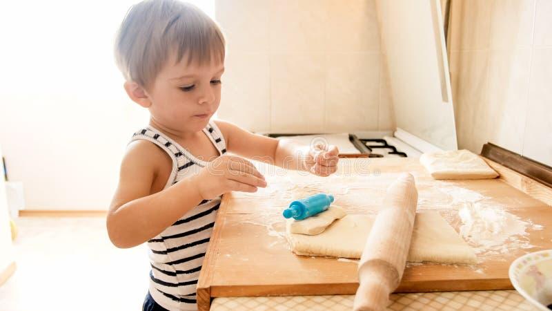 Zbli?enie portret 3 roku berbe? ch?opiec pozycji na kuchni i kulinarnym cie?cie Dziecka pieczenie i robi? ?niadanie zdjęcia stock