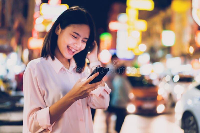 Zbli?enie trzyma smartphone przy noc? na miasto zakupy ulicie kobieta i ludzie, chodzimy zdjęcie stock