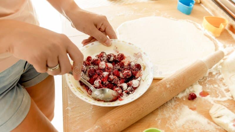 Zbli?enie wizerunek miesza cukier z jagodami m?oda kobieta Gospodyni domowa robi jagodowemu kumberlandowi dla s?odkiego kulebiaka obraz stock