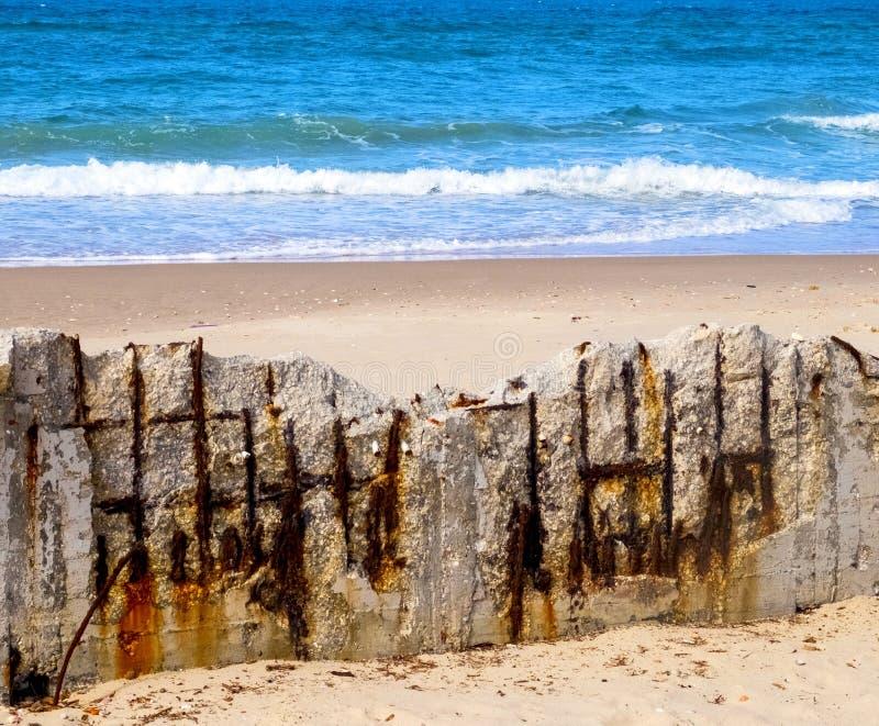 Zbrojona betonowa struktura na plaży, załamujący się od wilgoci i korodowania obraz royalty free