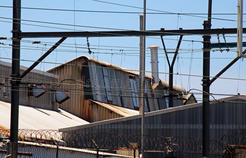 ZBUTWIAŁY FABRYCZNY budynku dach ZA ogrodzeniem ochronnym I kolej kablami obrazy stock