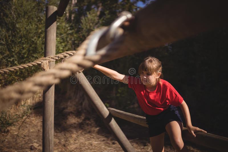 Zdecydowana dziewczyna ćwiczy na plenerowym wyposażeniu podczas przeszkoda kursu zdjęcia stock