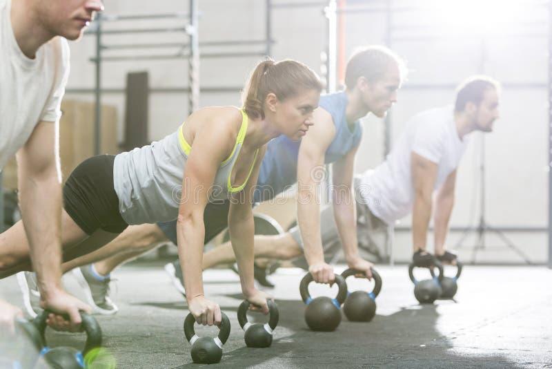 Zdecydowani ludzie robi pushups z kettlebells przy crossfit gym fotografia royalty free