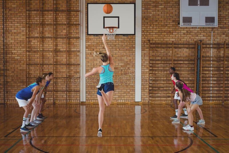 Zdecydowani szkoła średnia dzieciaki bawić się koszykówkę zdjęcie royalty free