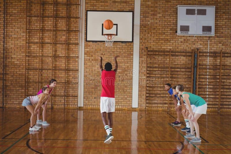 Zdecydowani szkoła średnia dzieciaki bawić się koszykówkę obrazy stock
