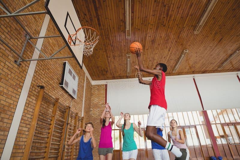 Zdecydowani szkoła średnia dzieciaki bawić się koszykówkę fotografia stock