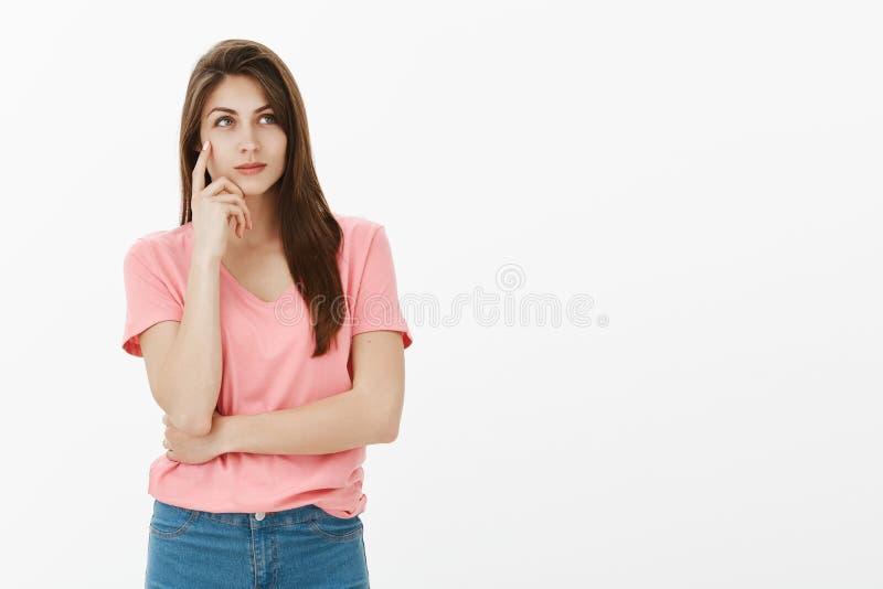 Zdecydowany mądrze atrakcyjny żeński uczeń w różowej koszulce, trzyma palec wskazującego na świątynnym i uśmiechniętym podczas gd zdjęcie royalty free