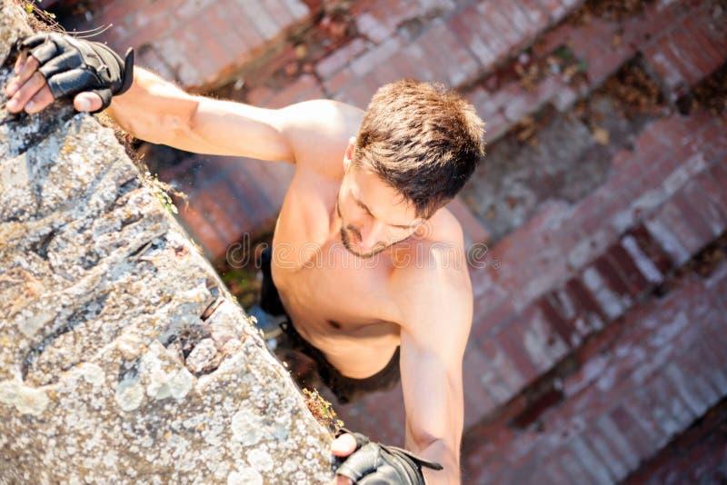 Zdecydowany młody człowiek wspina się ścianę podczas gdy bezpłatny bieg obraz stock