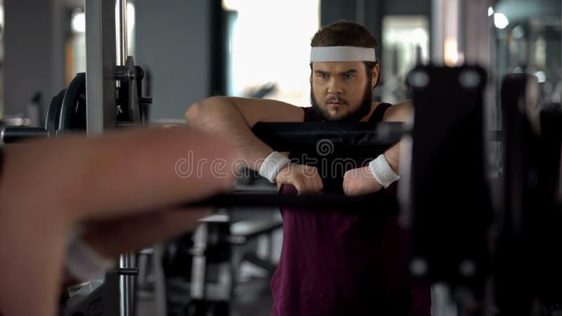 Zdecydowany pyzaty mężczyzna pozuje przy lustrem jako silna atleta, trening motywacja fotografia stock