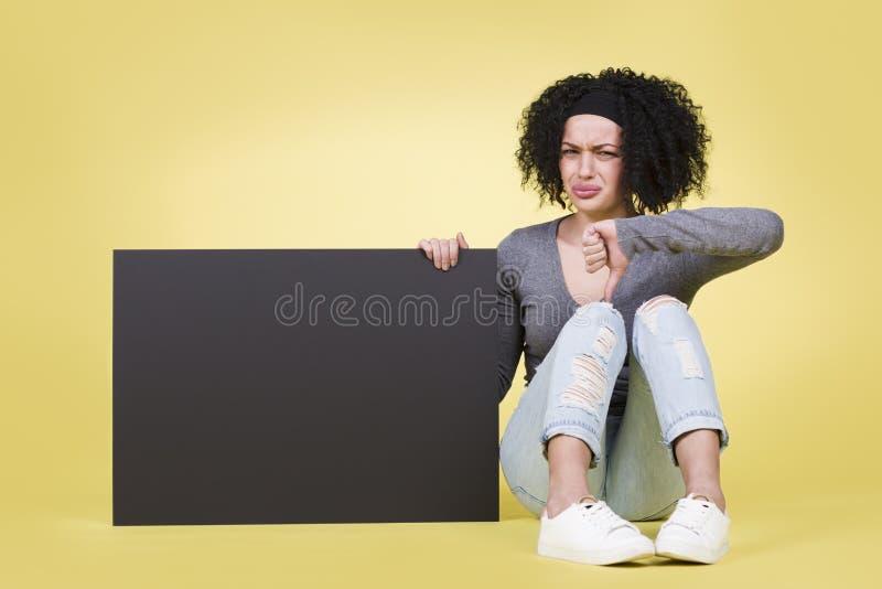 Zdegustowana dziewczyna daje kciukom zestrzela trzymać czarną znak deskę zdjęcia stock