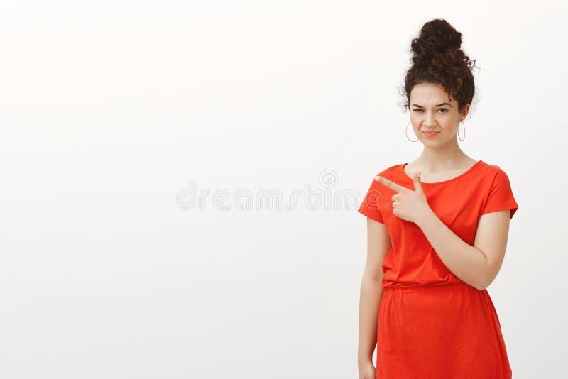 Zdegustowana europejska kobieta w eleganckiej przypadkowej czerwieni sukni składa wargi i marszczy brwi, patrzeje spod czoła podc zdjęcia royalty free
