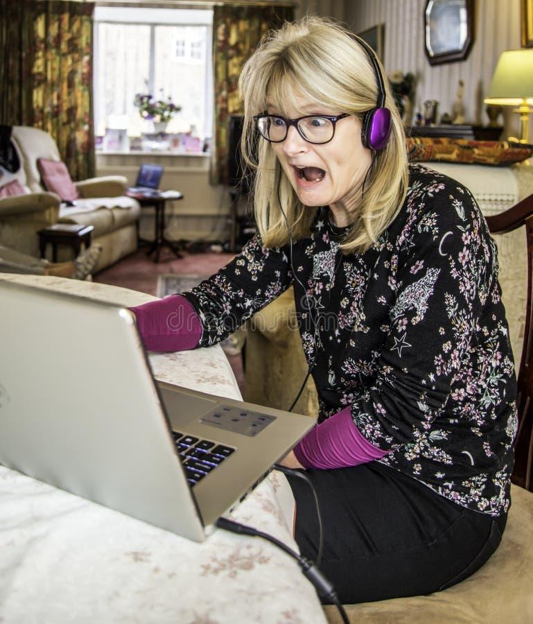 Zdegustowana kobieta, jest ubranym hełmofony, szokował przy co widzii online na jej laptopie obraz royalty free