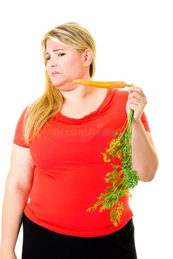 Zdegustowana młoda kobieta trzyma surowej marchewki fotografia stock