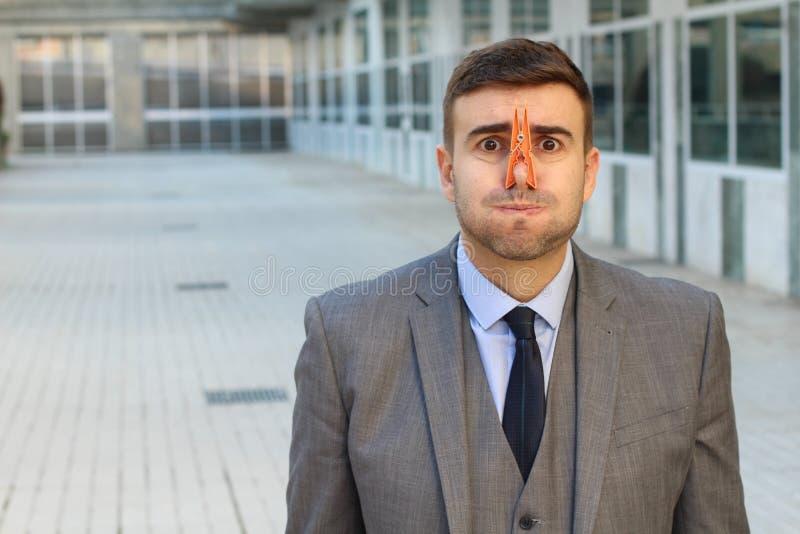 Zdegustowany biznesmen z clothespin w jego nosie zdjęcie royalty free