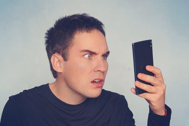 Zdegustowany mężczyzna czyta wiadomość tekstową facetów spojrzenia przy smartphone ekranem w niespodziance Emocja cud złość i ans zdjęcia stock