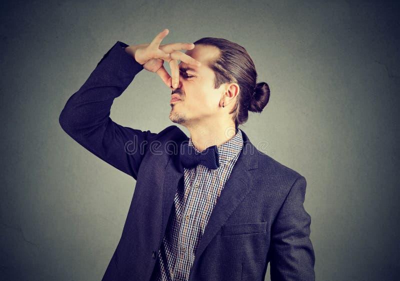 Zdegustowany mężczyzna nękań nos z palców spojrzeniami z obmierzłością coś śmierdzi obraz stock