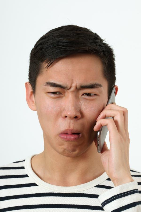 Zdegustowany młody Azjatycki mężczyzna używa smartphone fotografia stock