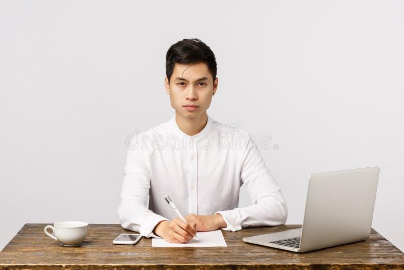 Zdeterminowany i asertywny, pracowity młody przedsiębiorca azjatycki w biurze, papier do pisania na biurku, wyglądający na pewneg obrazy royalty free