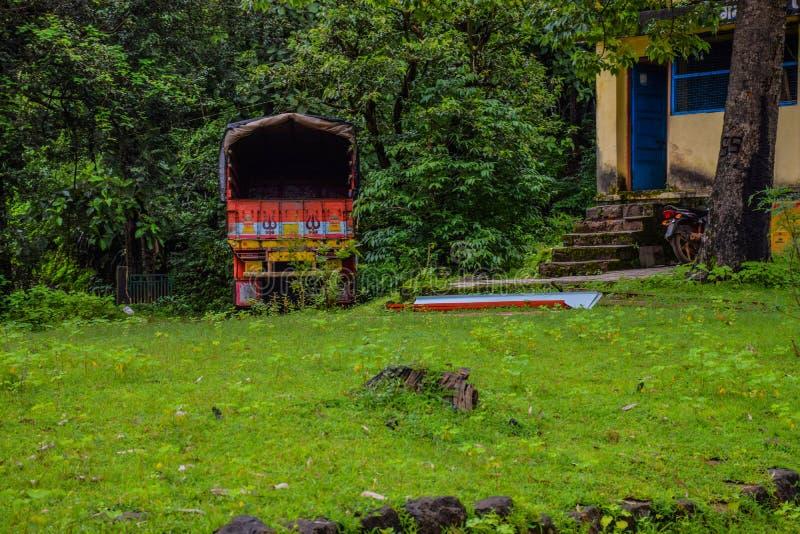 Zdjęcie samochodu ciężarowego zaparkowanego w gęsto zielonym lesie w Indiach obraz stock