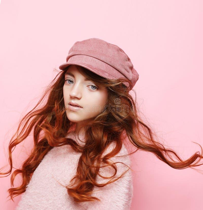Zdjęcie szczęśliwej nastolatki, stojącej samotnie na różowym tle, w różowym kapeluszu i swetrze. Koncepcja stylu życia i  fotografia stock