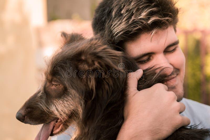 Zdjęcie z archiwum młodego mężczyzny przytulającego brązowego psa, przyjazne zwierzę koncepcyjne, najlepszych przyjaciół zdjęcie stock