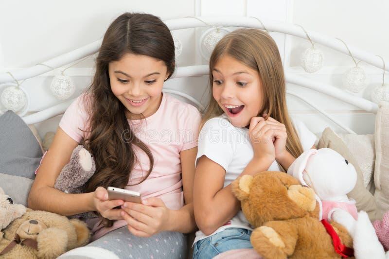 Zdobycza szczęśliwy moment Dziewczęcego czasu wolnego szczęśliwy dzieciństwo Dziewczyny z smartphone używają nowożytną technologi zdjęcia stock