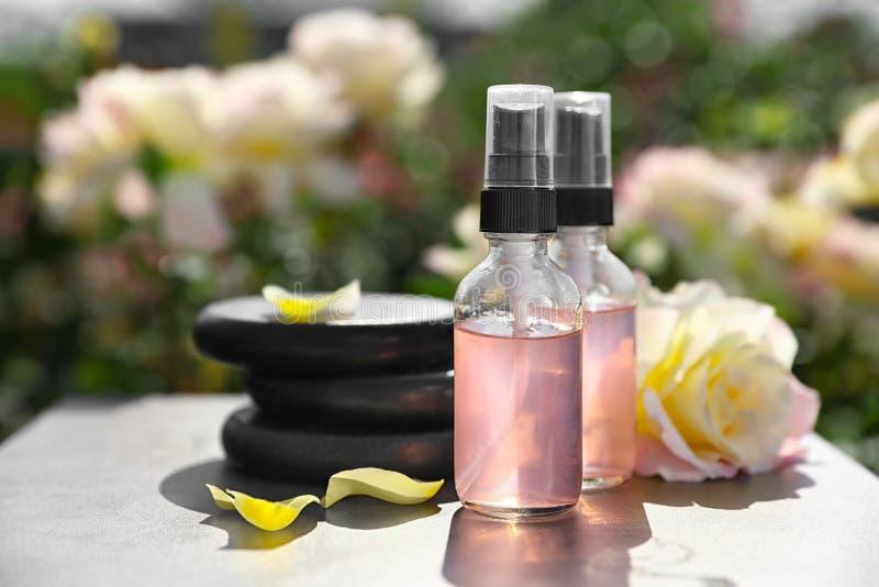 Zdrój dryluje i wzrastał na stole w ogródzie, butelki toner z istotnym olejem Harmonia i zen zdjęcie stock