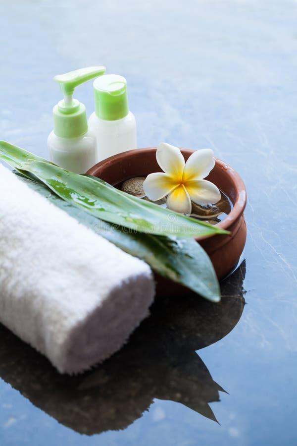 Zdrój lub wellness położenie z tropikalnym kwiatem, pucharem woda, ręcznikiem i kremową tubką na ciemnym tle, fotografia stock
