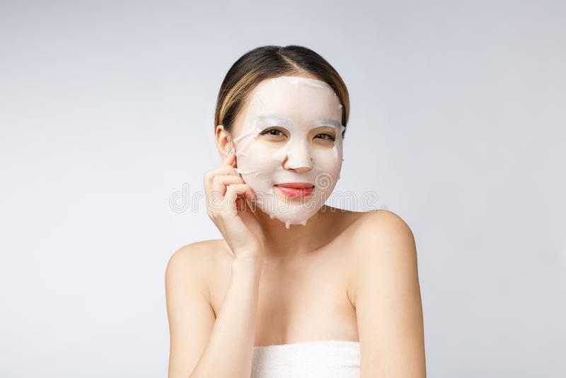 Zdrój, opieka zdrowotna Azjatycka dziewczyna z kosmetyczną maską odizolowywa na bielu fotografia stock