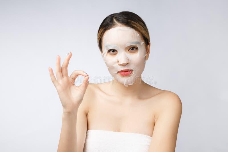 Zdrój, opieka zdrowotna Azjatycka dziewczyna z kosmetyczną maską odizolowywa na bielu zdjęcia royalty free