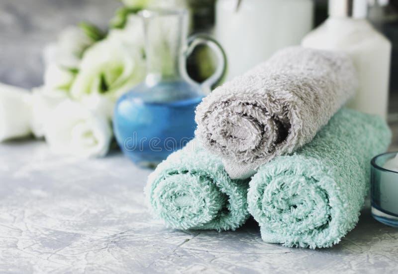 Zdrój ustawiający na białym marmuru stole z stertą ręczniki, selekcyjna ostrość zdjęcie stock