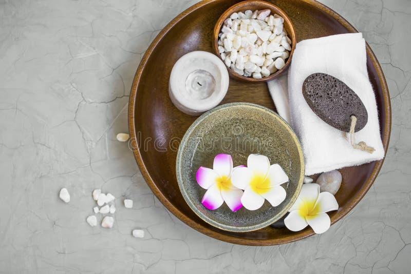 Zdrojów produkty w drewnianej tacy, odgórny widok zdrój rzeczy z frangipani kwiatami, świeczka, kąpielowa sól, ręcznik i ponce ka zdjęcie royalty free