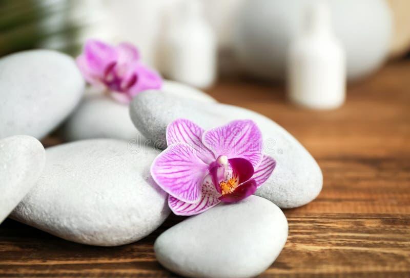 Zdrojów kamienie i piękna orchidea kwitną na drewnianym stole, zbliżenie fotografia stock