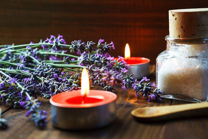 Zdroju masażu położenie z lawenda kwiatami, perfumowymi aromat świeczkami i kosmetyk solą na drewnianym tle, obrazy stock