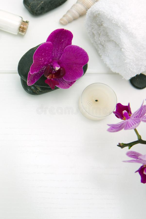 Zdroju położenie z różowymi orchideami, czerń kamieniami i kąpielowymi solami na drewnianym tle, zdjęcia royalty free