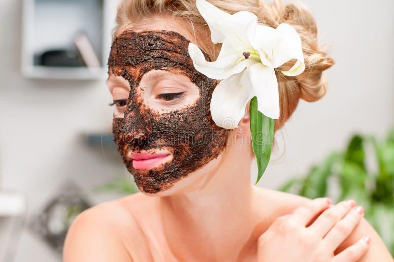 Zdroju salon Piękna kobieta z czekoladową twarzową maską przy piękno salonem fotografia stock