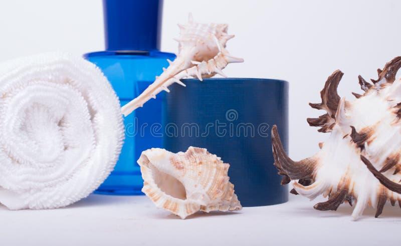 Zdroju salonu pojęcie z staczającym się białym ręcznikiem, błękitną butelką i seashells na białym drewnianym tle, zamkniętego ost zdjęcia stock