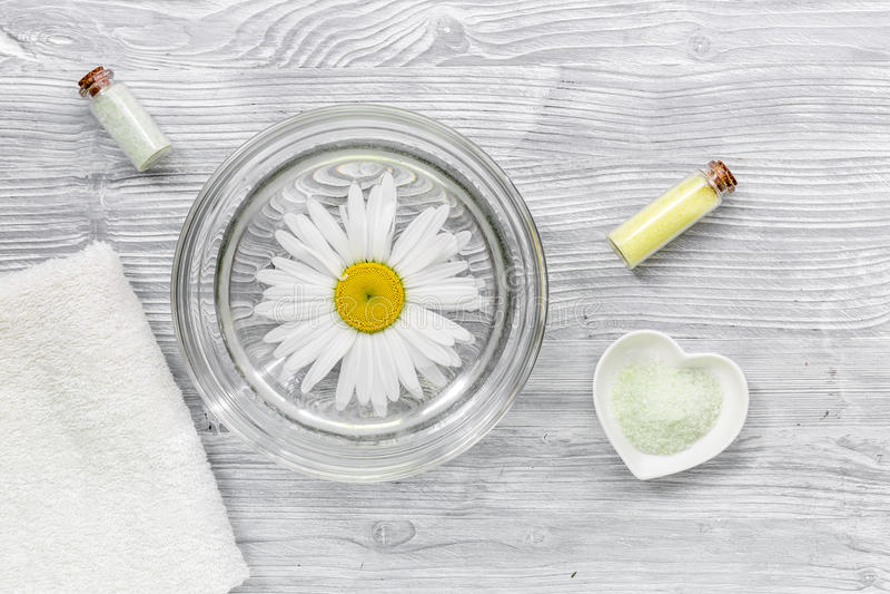 Zdroju skład na drewnianym biurku z chamomile, ręcznikiem i butelkami z solankowym odgórnym widokiem, obraz stock
