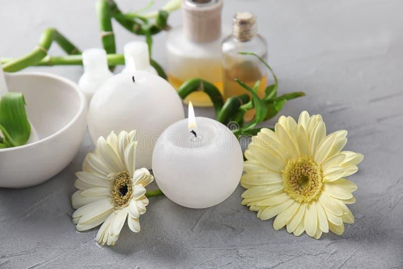 Zdroju skład z świeczkami i kwiatami na popielatym tle zdjęcia royalty free
