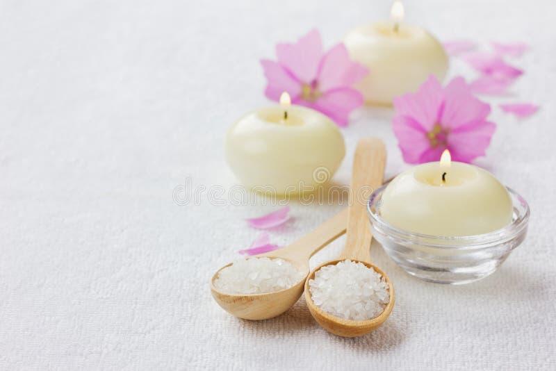 Zdroju skład z morze soli skąpaniem w drewnianej łyżce, menchia kwiatach i płonących świeczkach na białej powierzchni, zdjęcie royalty free