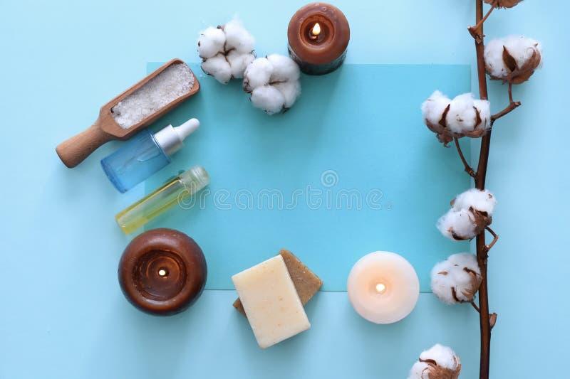 Zdroju skład z płonącymi świeczkami, kosmetykami i bawełną, kwitnie na koloru tle obraz royalty free