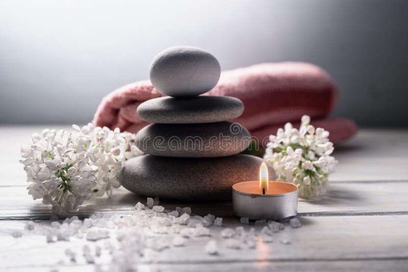 Zdroju wciąż życie z ostrosłupem zen kamienie, płonąca świeczka, morze sól, ręcznik i biali kwiaty na białym drewnianym stole, fotografia royalty free