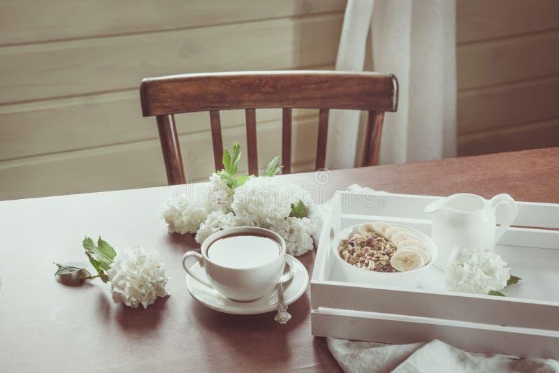 Zdrowa śniadaniowa filiżanka kawy, granola i wystrój z kwiatami, Nieociosany wnętrze obraz stock