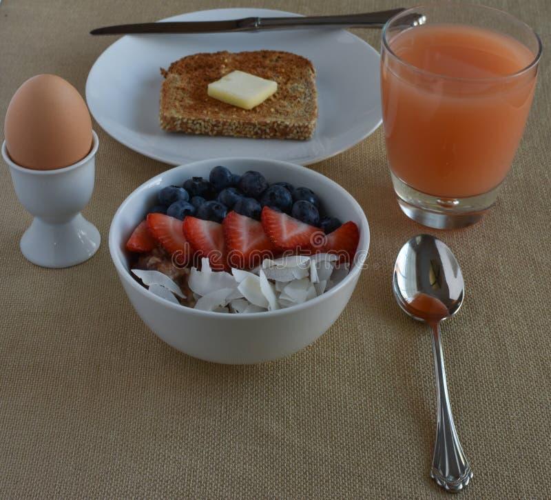 Zdrowa Śniadaniowa scena z grapefruite sokiem, gotowanym jajkiem, kiełkującą zbożową grzanką i stali rżniętym oatmeal z owoc, obraz stock