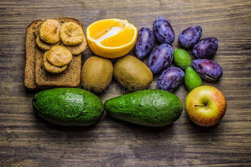 zdrowa żywność Świeże owoc na drewnianym stole Plasterki chleb, banan, pomarańcze, kiwi, figi, feijoa i śliwki, fotografia stock