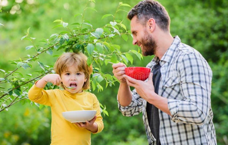 Zdrowa żywność i dieta To powinno być w porządku szczęśliwi ojcowie Mały chłopiec z tatą je płatki Obligacje rodzinne Cieszące si zdjęcie stock