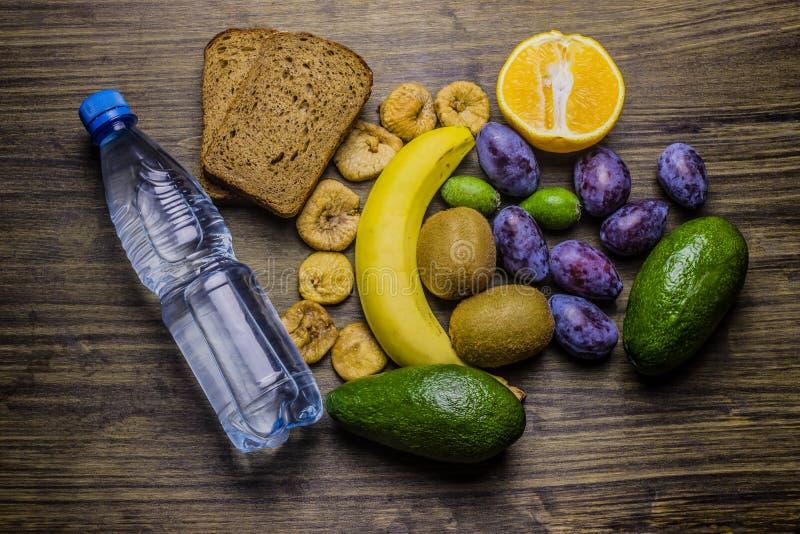 zdrowa żywność Zdrowy jedzenie na stole dla przekąski woda butelka Plasterki chleb, banan, pomarańcze, kiwi, figi, feijoa i zdjęcie royalty free