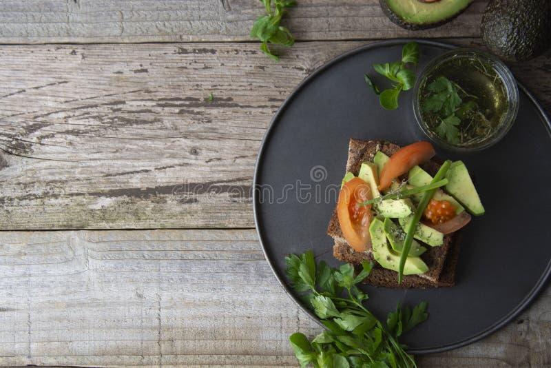 Zdrowa avocado kanapka na ciemnym żyto grzanki chlebie robić z świeżym pokrojonym avocado, ziarnami i pomidorami, na nieociosanym obraz stock
