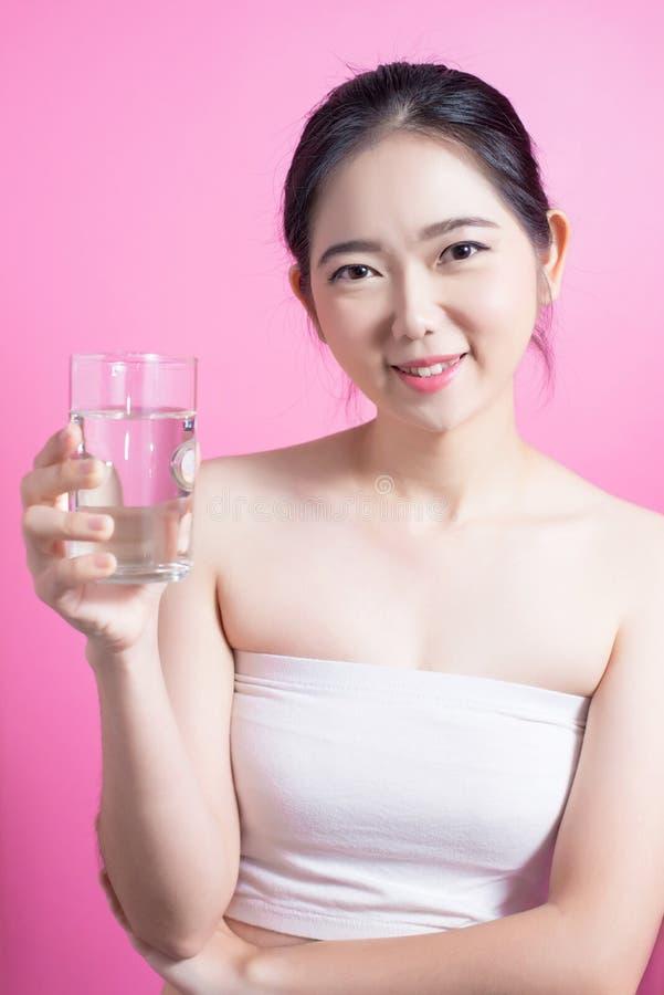 Zdrowa azjatykcia młoda piękna kobiety woda pitna, piękno twarzy naturalny makeup, odizolowywający nad różowym tłem zdjęcie royalty free