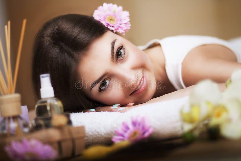 Zdrowa dziewczyna relaksuje na masażu stole Przed procedurą w zdroju Masażysta iść masować jego z powrotem ciało opieki zdrowia s zdjęcia stock
